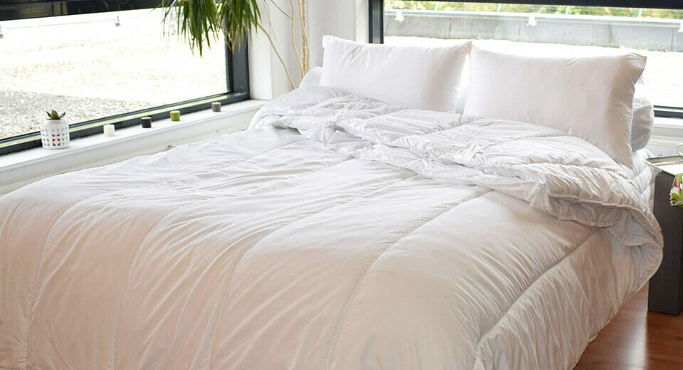 piumino e cuscino letto bianco
